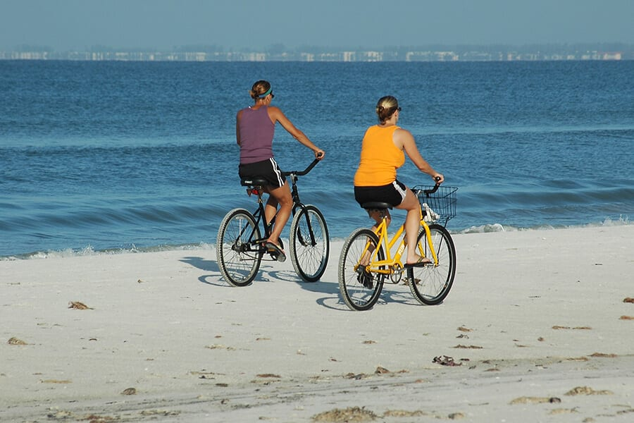 Two people riding bikes on beach
