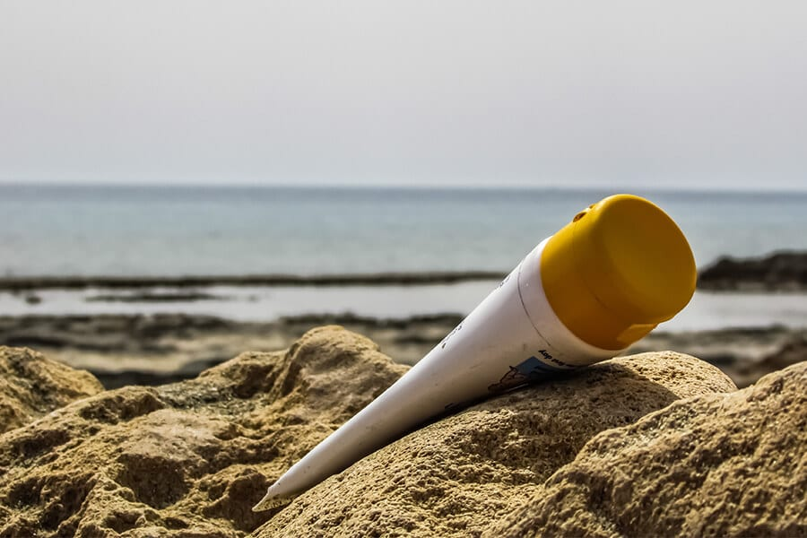 Bottle of sunscreen on the beach.