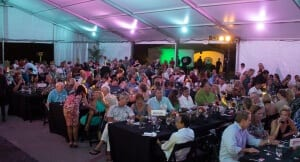 Guests gather in colorfully lit tent for dinner