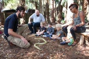 Zookeeper introducing kids and parents to a snake