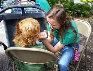 Zoo teen painting a guest's face