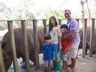 Family posing with rhinos