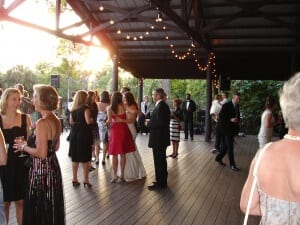 Guests mingle on the deck at sunset