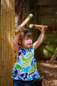 Girl playing with bamboo wind chime