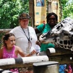 Volunteers helping guests during giraffe feeding encounter