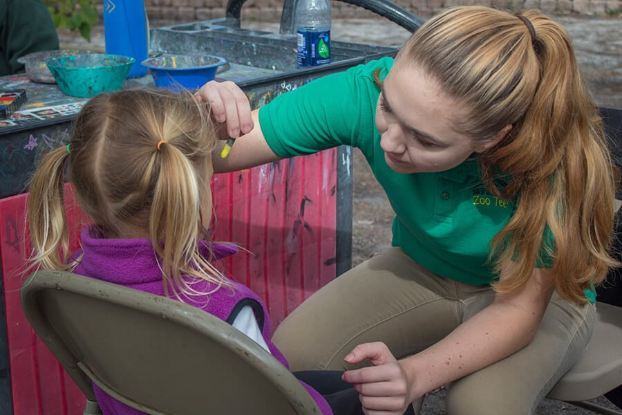 Zoo teen Haven painting the face of a young Zoo guest